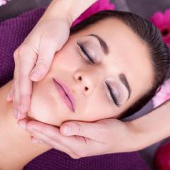 entspannte junge frau bei einer gesichts kopf massage
